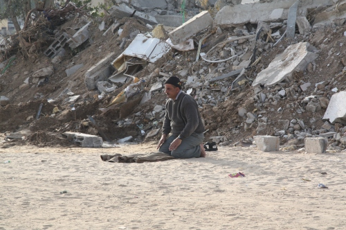 With the backdrop of mounds of rubble and tents was another man, praying, on a piece of tarp. While the Israelis had taken away everything else of his, they did not take away his God, and to this, he bowed his head in gratitude.